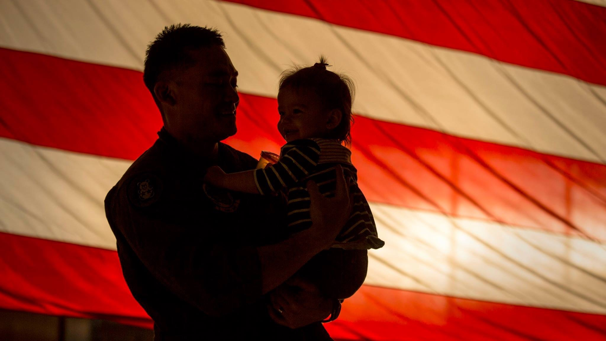Marine with his daughter in front of U.S. flag